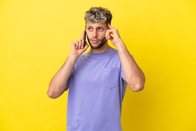 Jovem homem caucasiano usando telefone celular isolado em um fundo amarelo, tendo dúvidas e pensando