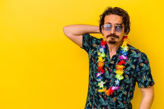 Jovem homem caucasiano usando um colar havaiano isolado na parede amarela tocando a parte de trás da cabeça, pensando e fazendo uma escolha.