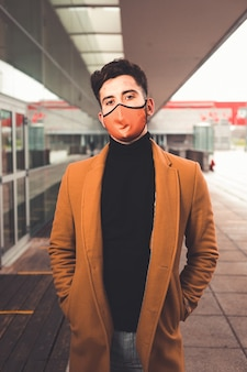 Jovem homem caucasiano usando uma máscara marrom com um casaco marrom na rua