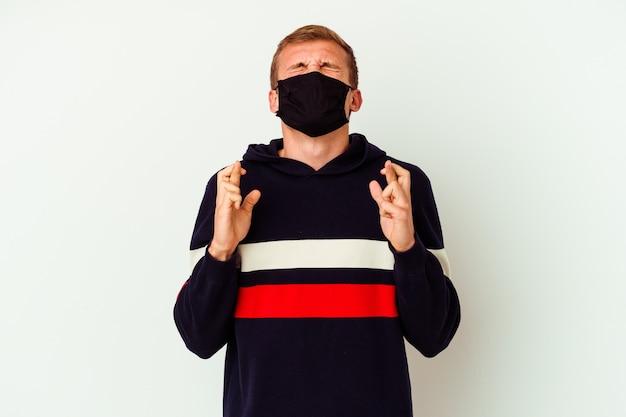 Jovem homem caucasiano usando uma máscara para vírus isolado no branco cruzando os dedos para ter sorte