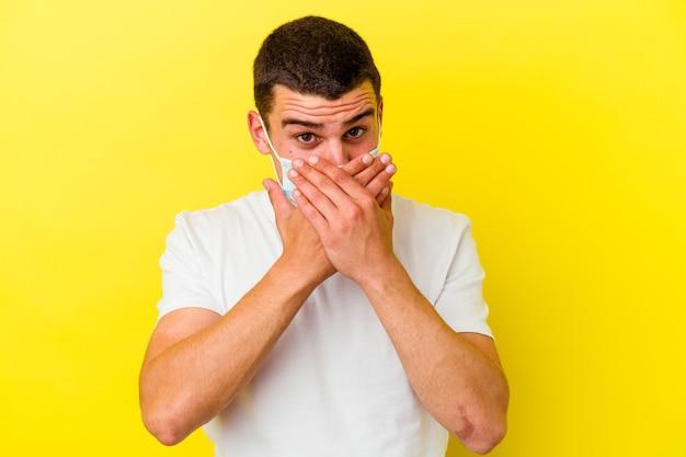 Jovem homem caucasiano usando uma proteção para coronavírus isolado na parede amarela chocado cobrindo a boca com as mãos