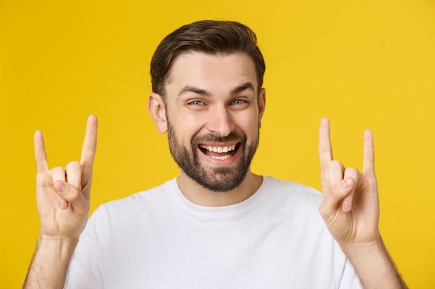 Jovem homem caucasiano vestindo camiseta casual sobre amarelo isolado gritando com expressão maluca fazendo o símbolo do rock com as mãos para cima