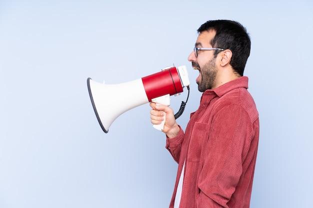 Jovem homem caucasiano vestindo jaqueta de veludo sobre parede azul, gritando através de um megafone