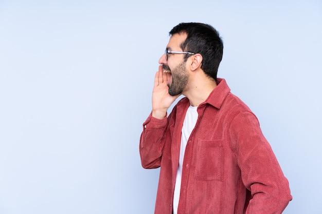 Jovem homem caucasiano vestindo jaqueta de veludo sobre parede azul, gritando com a boca aberta para a lateral