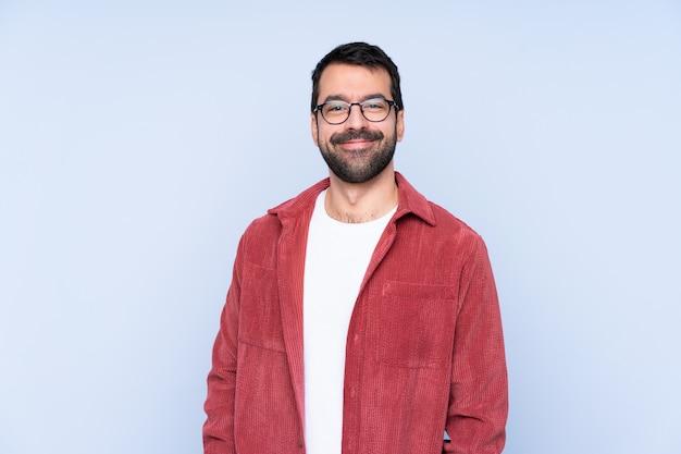 Jovem homem caucasiano vestindo jaqueta de veludo sobre parede azul rindo