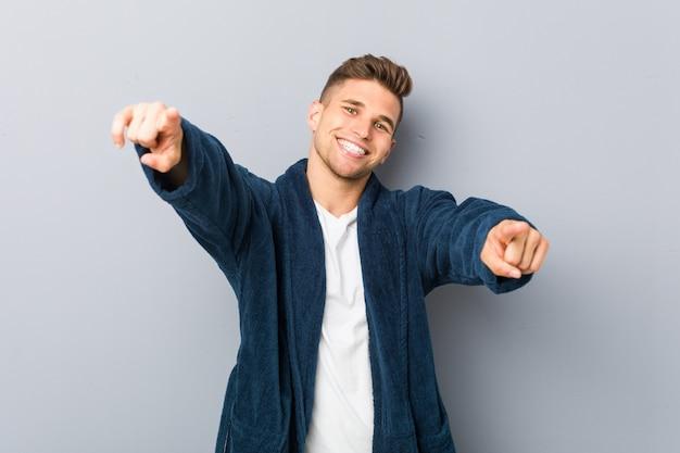 Jovem homem caucasiano vestindo pijama alegre sorrisos apontando para a frente.