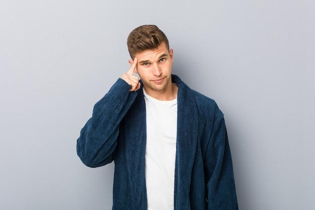Jovem homem caucasiano vestindo pijama apontando o templo com o dedo, pensando, focado em uma tarefa.