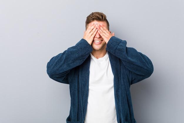 Jovem homem caucasiano vestindo pijama cobre os olhos com as mãos, sorri amplamente esperando por uma surpresa.
