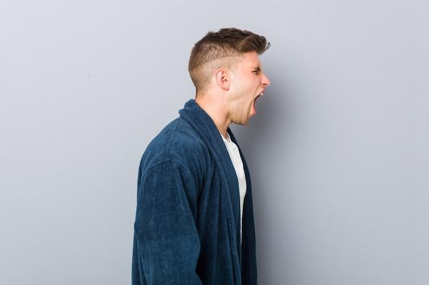 Jovem homem caucasiano vestindo pijama gritando para um espaço de cópia