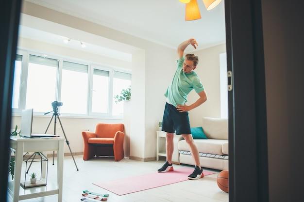 Jovem homem caucasiano vestindo roupas esportivas se aquecendo durante uma videochamada usando um laptop e uma câmera