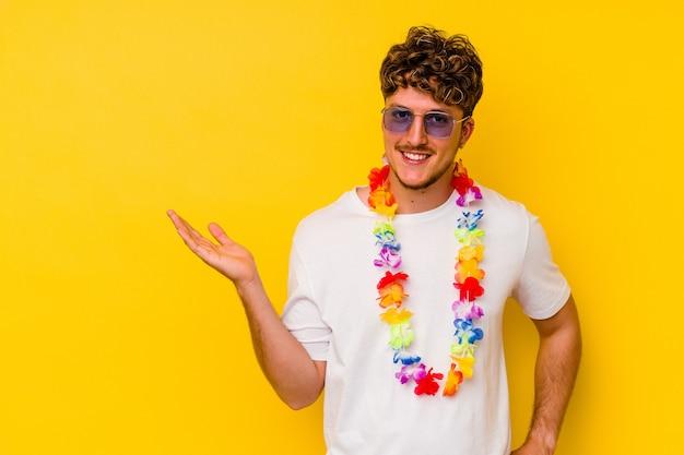 Jovem homem caucasiano vestindo um material de festa havaiana isolado em fundo amarelo, mostrando um espaço de cópia na palma da mão e segurando a outra mão na cintura.
