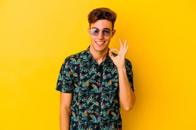 Jovem homem caucasiano, vestindo uma camisa havaiana em amarelo pisca um olho e segura um gesto de ok com a mão.