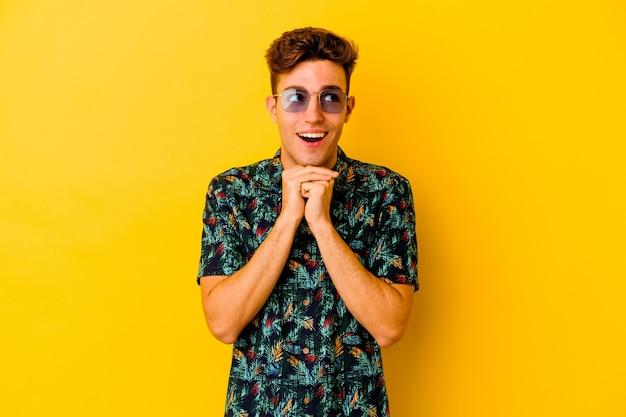 Jovem homem caucasiano, vestindo uma camisa havaiana isolada na parede amarela, mantém as mãos embaixo do queixo, olhando alegremente para o lado