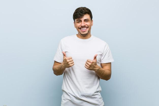 Jovem homem caucasiano, vestindo uma camiseta branca, levantando os dois polegares, sorrindo e confiante.