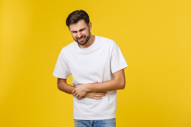 Jovem homem caucasiano vestindo uma jaqueta marrom doente, sofrendo de dor de estômago, conceito de doença dolorosa