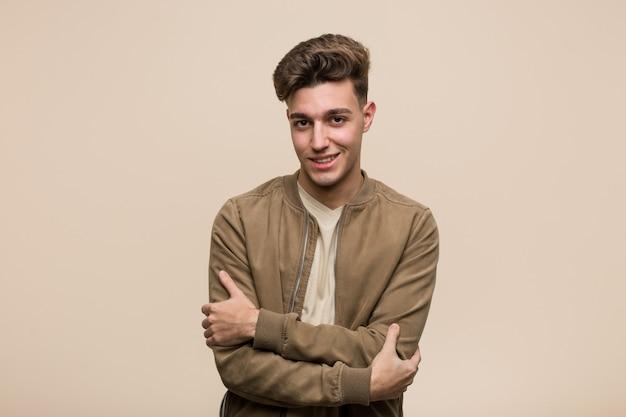 Jovem homem caucasiano, vestindo uma jaqueta marrom que se sente confiante, cruzando os braços com determinação.