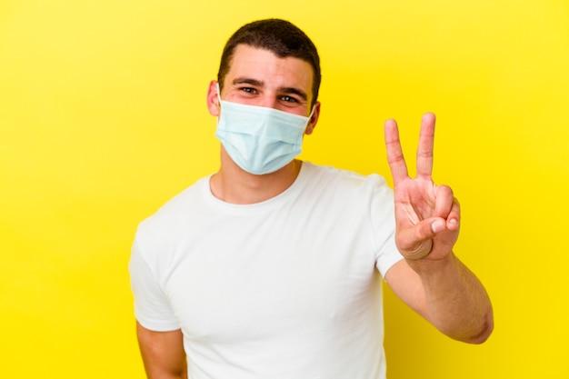 Jovem homem caucasiano vestindo uma proteção para coronavírus isolado e sorrindo amplamente.