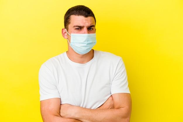 Jovem homem caucasiano vestindo uma proteção para coronavírus isolado na parede amarela, olhando para a câmera com uma expressão sarcástica