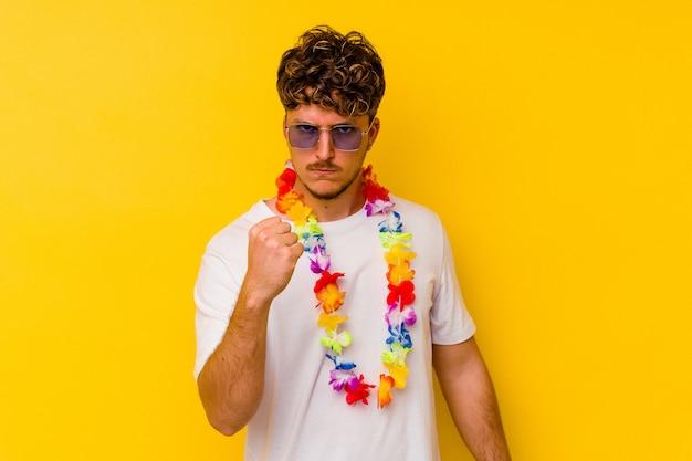 Jovem homem caucasiano vestindo uma roupa de festa havaiana isolada em fundo amarelo, mostrando o punho para a câmera, expressão facial agressiva.