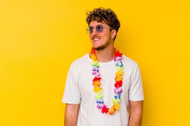 Jovem homem caucasiano vestindo uma roupa de festa havaiana isolada em um fundo amarelo, sonhando em alcançar objetivos e propósitos