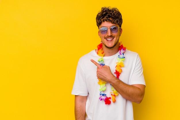 Jovem homem caucasiano vestindo uma roupa de festa havaiana isolada no fundo amarelo, sorrindo e apontando para o lado, mostrando algo no espaço em branco.