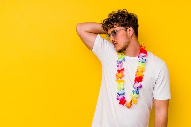 Jovem homem caucasiano vestindo uma roupa de festa havaiana isolada no fundo amarelo, tocando a parte de trás da cabeça, pensando e fazendo uma escolha.