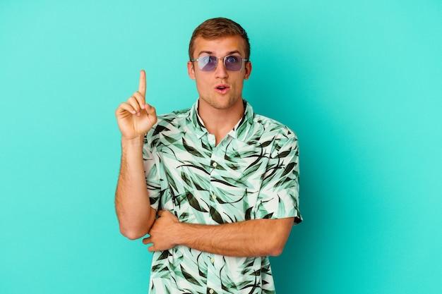 Jovem homem caucasiano vestindo uma roupa de verão, isolado no fundo azul, tendo uma ótima ideia, o conceito de criatividade.