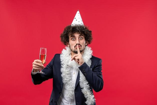 Jovem homem celebrando o ano novo de frente na parede vermelha feriado humano natal