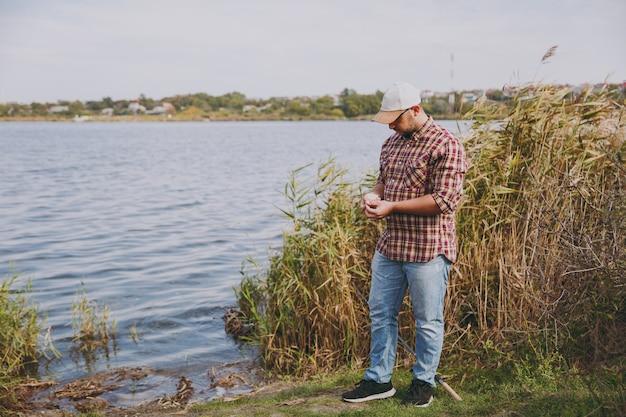 Jovem homem com a barba por fazer em camisa quadriculada, boné e óculos de sol parece e puxa a isca de larvas da pequena caixa contra o fundo do lago, arbustos, juncos. estilo de vida, recreação do pescador, conceito de lazer.