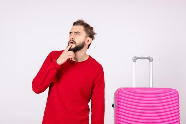 Jovem homem com bolsa rosa na parede branca fotografia de viagem em cor humana viagem de férias de frente