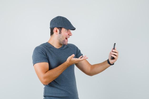 Jovem homem com boné de camiseta falando no chat de vídeo e parecendo surpreso