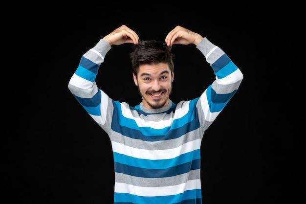 Jovem homem com camisa listrada de frente e puxando o cabelo na parede preta