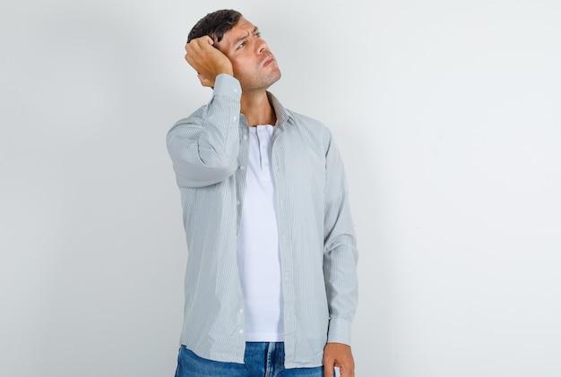 Jovem homem com camiseta cinza, jeans olhando para cima com a mão na cabeça e parecendo pensativo