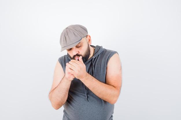 Jovem homem com capuz sem mangas, boné fumando enquanto posa e parece confiante, vista frontal.
