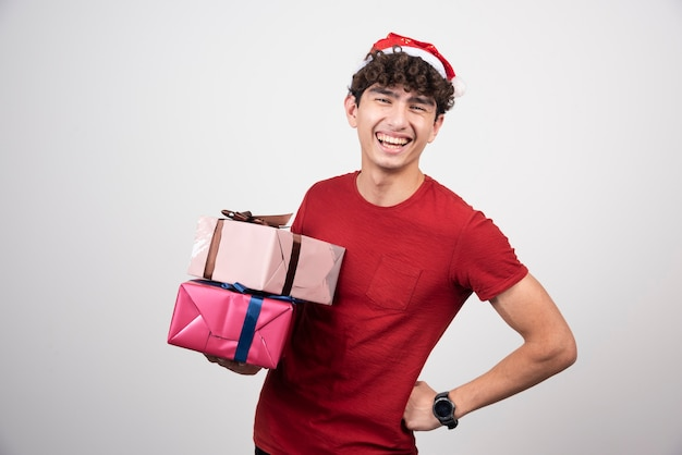 Jovem homem com chapéu de papai noel segurando presentes