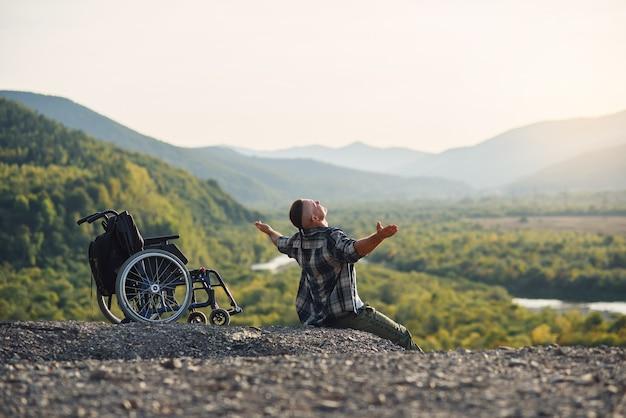 Jovem homem com deficiência, sentado na montanha perto de uma cadeira de rodas, com as mãos levantadas, apreciando o ar fresco e a beleza da natureza