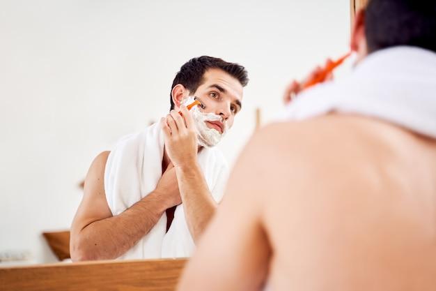 Jovem homem com espuma na barba faz a barba perto do espelho pela manhã