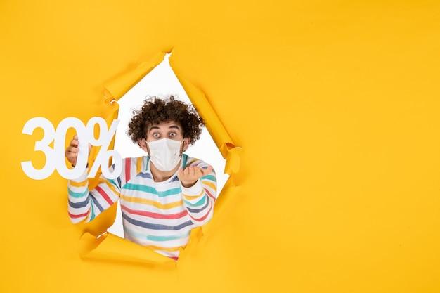 Jovem homem com máscara e segurando vírus covide foto-pandêmico de cor amarela