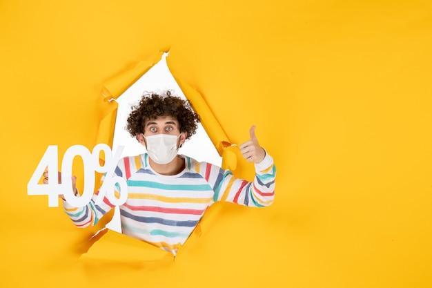 Jovem homem com máscara, segurando a escrita na cor da pandemia de vírus amarelo, comprando fotos secretas