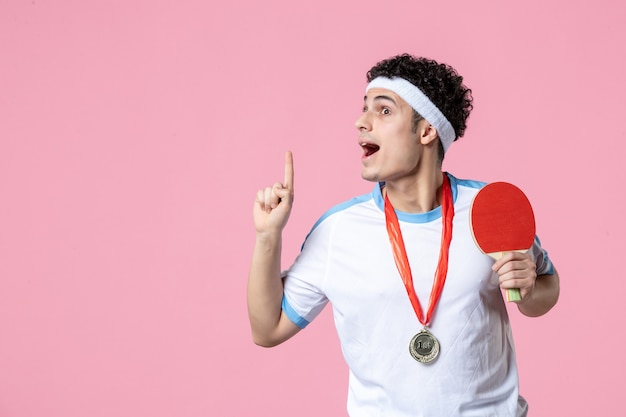 Jovem homem com roupas esportivas e medalha na parede rosa