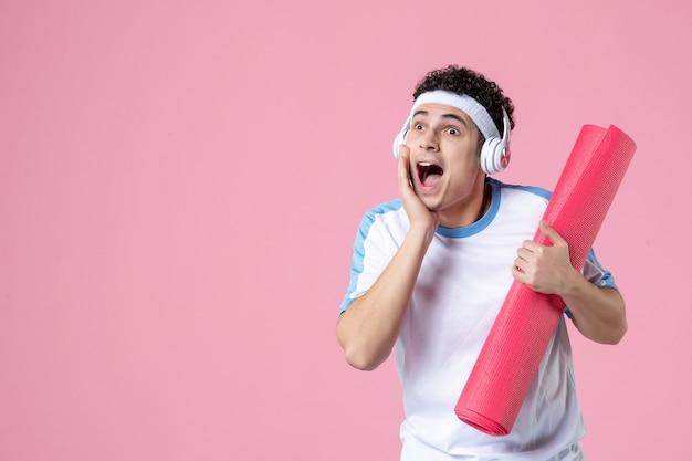 Jovem homem com roupas esportivas e tapete de ioga na parede rosa