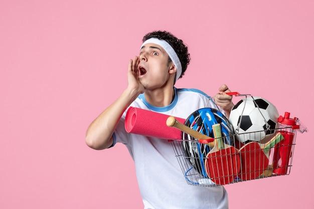 Jovem homem com roupas esportivas e uma cesta cheia de coisas esportivas na parede rosa