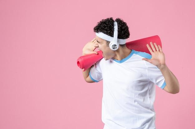 Jovem homem com roupas esportivas, tapete de ioga e fones de ouvido na parede rosa