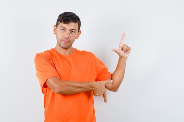 Jovem homem com uma camiseta laranja apontando para cima e para baixo e parecendo sensato