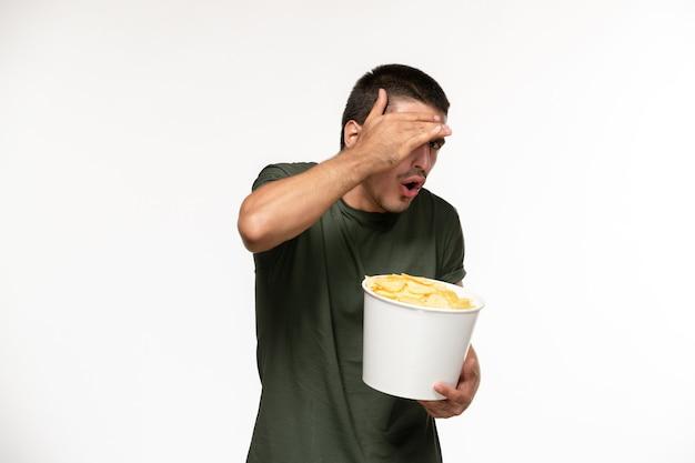 Jovem homem com uma camiseta verde segurando batata cips de frente assistindo filme na parede branca filme de pessoa solitária cinema
