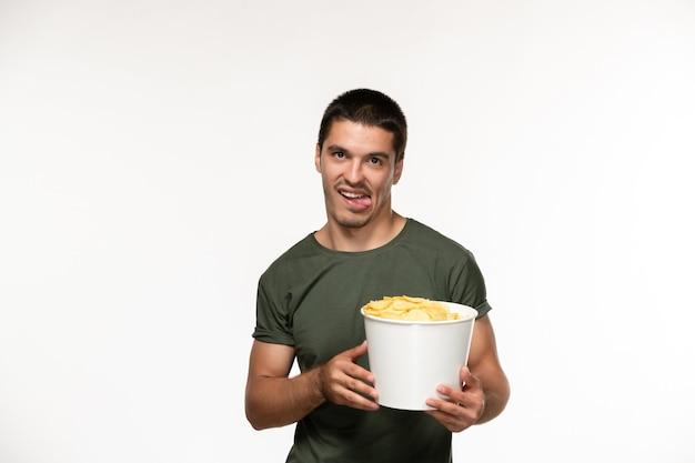 Jovem homem com uma camiseta verde segurando batatas cips de frente assistindo filme na parede branca-clara filme pessoa solitária cinema