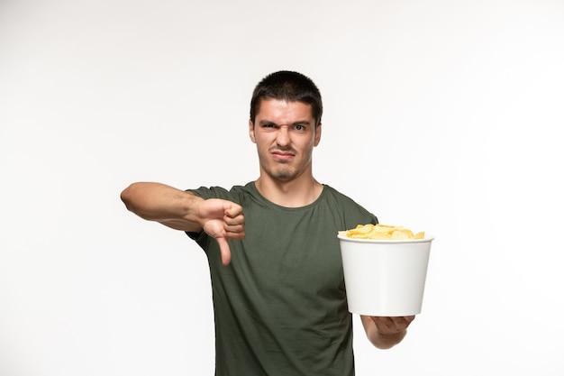 Jovem homem com uma camiseta verde segurando batatas cips mostrando uma placa na parede branca