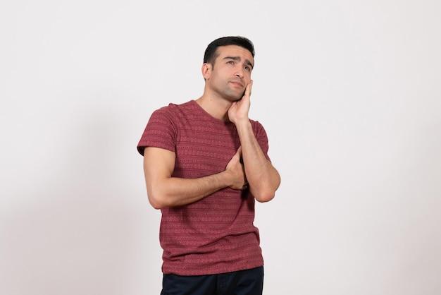 Jovem homem com uma camiseta vermelha escura, de frente para o outro, posando e pensando em um fundo branco