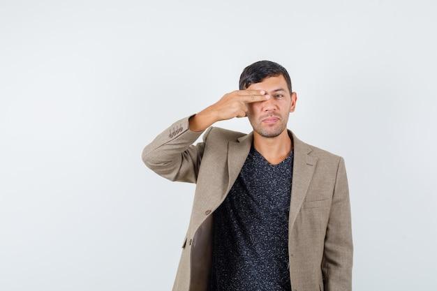 Jovem homem com uma jaqueta marrom acinzentada, camisa preta fechando seu olho com a mão e parecendo estranho, vista frontal.