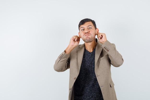 Jovem homem com uma jaqueta marrom acinzentada, camisa preta puxando as orelhas enquanto incha as bochechas e parece estranho, vista frontal.